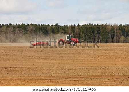 Red big wheeled tractor with large plough ploughs the land in a ploughed field on forest background at spring day, rural farm landscape #1715117455