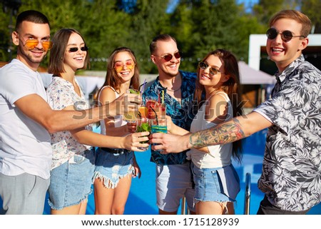 Group of friends having fun at poolside summer party clinking glasses with summer cocktails on sunny day near swimming pool. People toast drinking fresh juice at luxury villa on tropical vacation. #1715128939