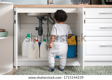 Little African-American baby playing with detergents at home. Child in danger Royalty-Free Stock Photo #1715144239