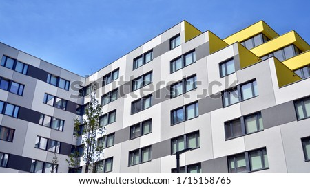 Contemporary residential building exterior in the daylight. Modern apartment buildings on a sunny day with a blue sky. Facade of a modern apartment building #1715158765