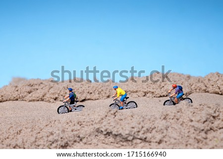 Cyclists ride on sand. Close up. Travelers with bikes. Motocross/ road and mountain cycle sport illustration. Mountain biking. Mini world figurine. #1715166940