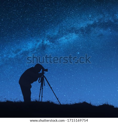 Silhouette of photographer with photo camera on a tripod shooting the Milky Way in a starry night sky. Long exposure, night shooting. #1715169754