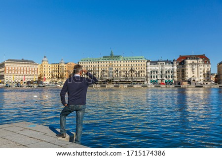 Stockholm, a man looks at the waterfront and architecture of the city #1715174386