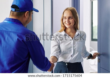 Smiling beautiful young woman opening entrance door and greeting repairman Royalty-Free Stock Photo #1715175604