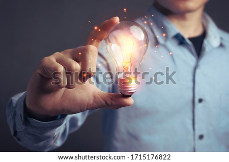 Man holding light bulbs, ideas of new ideas beautiful creative and communicate the new inventions with innovative technology and creativity. concept creativity with bulbs that shine glitter Royalty-Free Stock Photo #1715176822