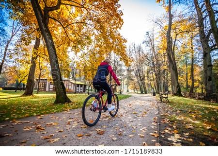 Urban biking - woman riding bike in city park  #1715189833