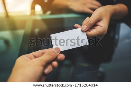 Two businessman holding and exchanging a blank business card