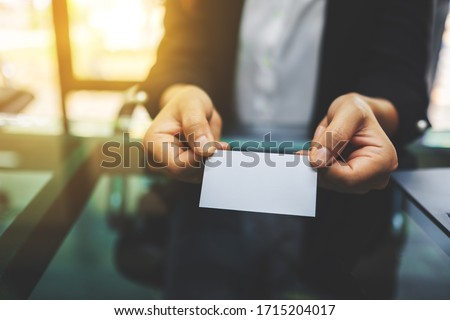 Businesswoman holding and giving a blank business card to someone