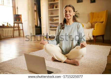 Zen, peace, balance, concentration and technology concept. Attractive senior woman sitting on carpet in front of open laptop keeping eyes closed and legs crossed, meditating to nature sounds #1715225077