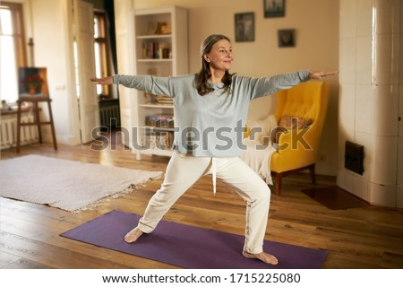 Full length shot of happy energetic mature woman in casual clothes exercising at home because of social distancing, practicing yoga on mat, standing in warrior ii pose. Age, wellness and health Royalty-Free Stock Photo #1715225080