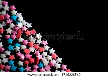 multicolored confectionery sprinkle in the form of stars on a black background #1715228560