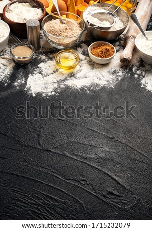 Baking ingredients for dough on black background, flour, eggs, butter, sugar and kitchen utensils for homemade baking. Cooking concept banner with copy space for text #1715232079