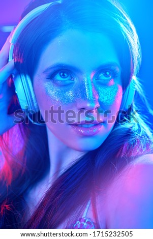 Party and holiday style. Pretty girl with shiny make-up and shiny dress listening to music in headphones and dancing in blue and pink light. #1715232505