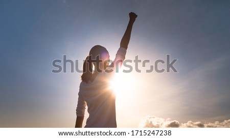 Strong woman with fist up to the sky. People, mental strength, power, victory, and never giving up concept.  Royalty-Free Stock Photo #1715247238
