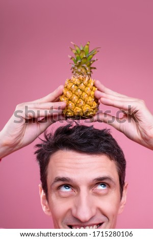 Vertical picture of happy weird man holding small pineapple with hands on head. Look up and smile. Isolated over pink background