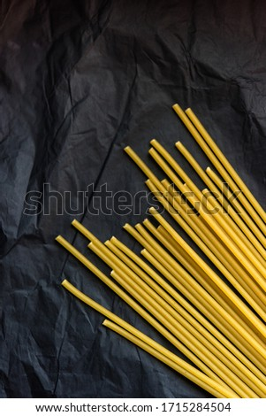 Vertical picture of bunch of raw dry uncooked pasta spaghetti lay on black crumpled paper background. Selective focus. Vegetarian food. Nutrition concept. Italian kitchen. Food preparation.
