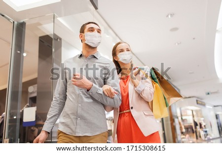 sale, consumerism and pandemic concept - happy young couple wearing face protective medical mask for protection from virus disease with shopping bags in mall #1715308615