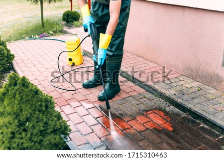 Man cleaning red, conrete pavement block using high pressure water cleaner. Paving cleaning concept. Man wearing waders, protective, waterproof trousers and gloves doing spring jobs in the garden. Royalty-Free Stock Photo #1715310463