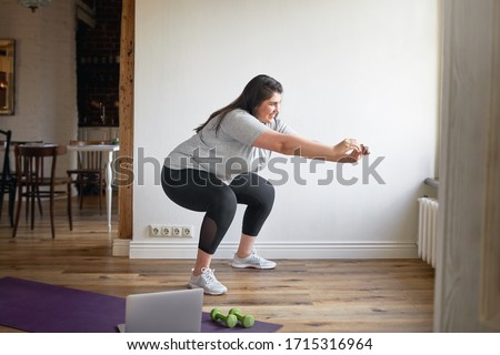 Beautiful female in sneakers and sports clothes exercising indoors, doing squats to burn fat, lose extra pounds, making body strong, watching instructional videos on laptop. Technology and fitness #1715316964