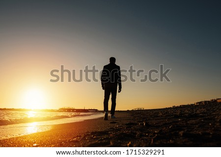 Silhouette of young man on the beach in Italy. Back view silhouette of a walking man running along on the beach at sunset with sun in the background. Man walking on the beach looking on sea at sunset. Royalty-Free Stock Photo #1715329291