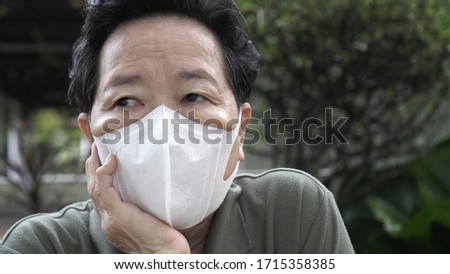 Asian Chinese elder wearing N95 mask protection from smog and Coronavirus #1715358385