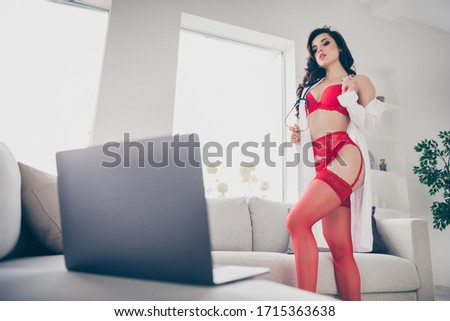 photo of hot slim desire lady work home quarantine private online notebook chat undressing play lover naughty nurse role take off lab coat look screen tender wear red bikini tights room indoors