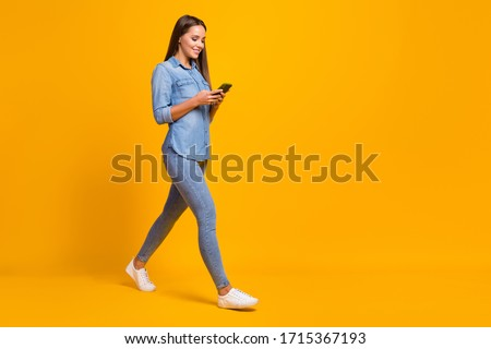 Full size profile side photo cheerful lovely pretty girl enjoy spring holiday use smartphone follow social network news wear good look shirt gumshoes isolated bright shine color background