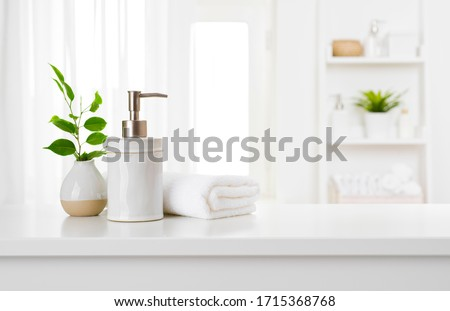 Soap dispenser and spa towel on pastel bathroom window interior #1715368768