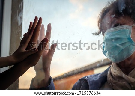 social distancing among the family, hand of the woman and her grandchildren on window plane, concept coronavirus and covid-19 pandemic Royalty-Free Stock Photo #1715376634