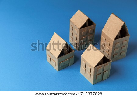 Cardboard houses on blue background, concept of small cozy city, friendly neighbors. Private property, real estate. #1715377828
