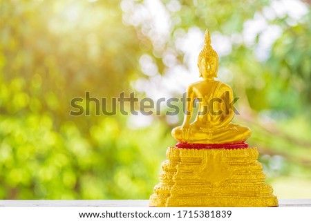 Close up portrait golden Buddha statue sitting on a golden base with green blurred nature background, Buddhist Sabbath Day concept.