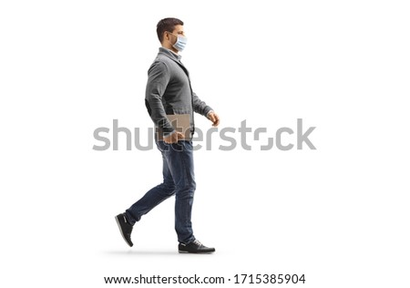 Full length profile shot of a man walking and wearing a protective medical mask isolated on white background #1715385904