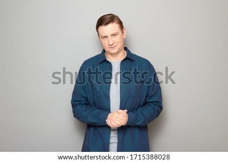 Studio portrait of confident satisfied man wearing casual blue shirt, smiling slightly, holding hands folded together, listening or waiting somebody, standing isolated over gray background #1715388028