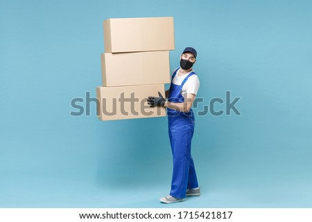 Full length delivery man in cap t-shirt uniform sterile face mask gloves isolated on blue background studio Guy employee courier hold box Service pandemic coronavirus virus covid-19 2019-ncov concept #1715421817