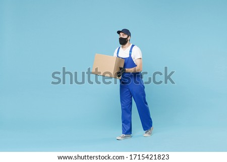 Full length delivery man in cap t-shirt uniform sterile face mask gloves isolated on blue background studio Guy employee courier hold box Service pandemic coronavirus virus covid-19 2019-ncov concept #1715421823