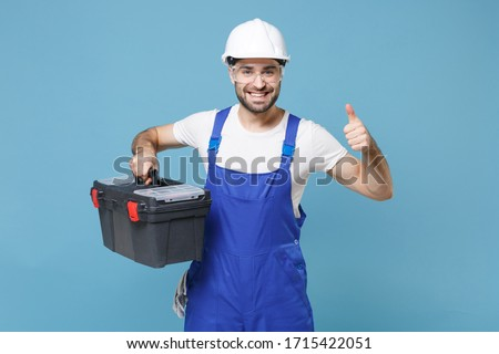 Smiling man in coveralls protective helmet hardhat glasses hold tool case box isolated on blue background. Instruments accessories for renovation apartment room. Repair home concept. Showing thumb up #1715422051