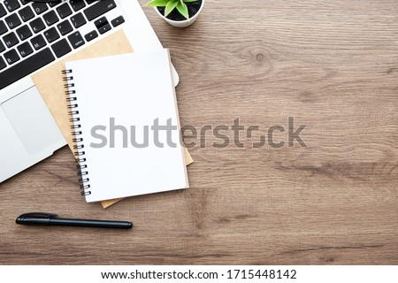 Blank notebook with pen are on top of wood office desk table with laptop computer, and supplies. Top view with copy space, flat lay. #1715448142