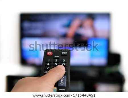Remote control and screen - binge watching the favorite TV show #1715448451