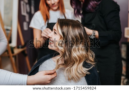 Beautiful hairstyle of young woman after dyeing hair and making highlights in hair salon. #1715459824