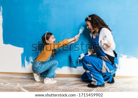 Mother and daughter enjoying together while painting wall. Royalty-Free Stock Photo #1715459902