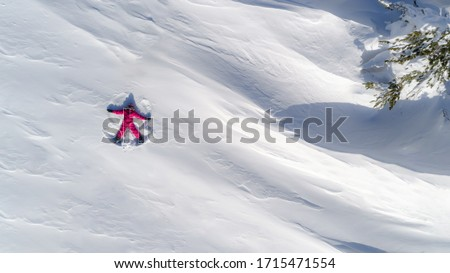 Top aerial view of young happy smiling girl making by arms snow angel figure and lying in snow, winter outdoor activity concept. Girl in the snow angel shows . Winter angel in a bright ski suit #1715471554
