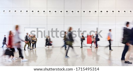 Many anonymous people walk in a corridor from the mall