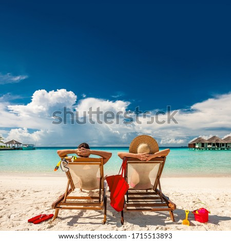 Couple in loungers on a tropical beach at Maldives #1715513893