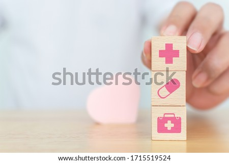Conceptual of health care and insurance. Wooden block cube shape on wood table with icon healthcare #1715519524