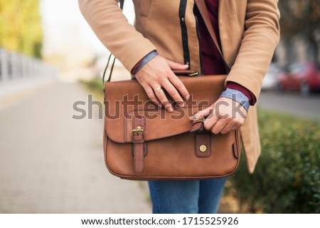 Close up of a businessman opening a briefcase while walking down the street. #1715525926