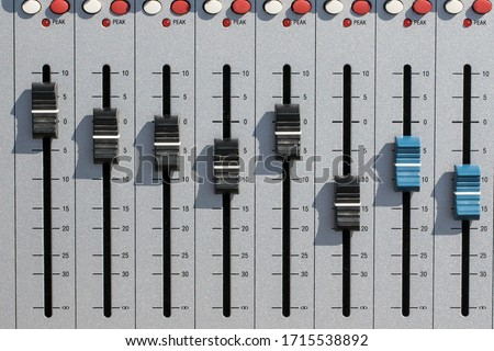 Sound mixing desk faders. Music studio recording equipment volume close-up image with peak LED and stereo master sliders. Home recording for musicians.