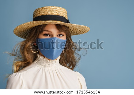 Woman wearing trendy spring, summer fashion outfit during quarantine of coronavirus outbreak. Model dressed protective stylish handmade face mask, straw hat, white blouse, earrings. Copy, empty space #1715546134