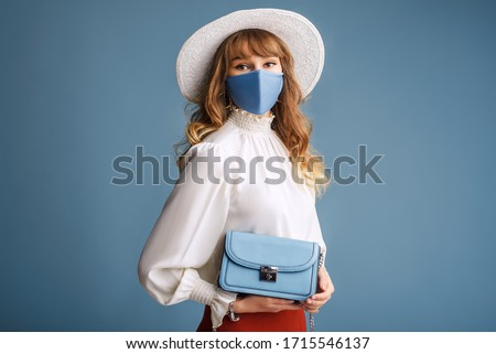Woman wearing trendy spring, summer fashion outfit during quarantine of coronavirus outbreak. Model dressed protective stylish handmade face mask, hat, holding small blue bag. Copy, empty space #1715546137