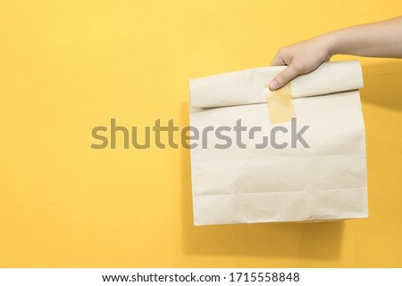 Close-up of a man's hand holding a bag to deliver #1715558848