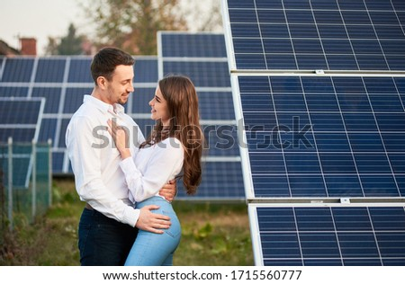 Beautiful man and woman looking at each other standing close to each other at solar plant, concept of healthy relationships #1715560777